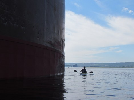 Deanna paddling next to a docked freighter